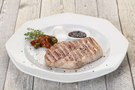 Grilled pork steak with pepper sauce served dried tomatoes and thyme Фото со стока - 129823797