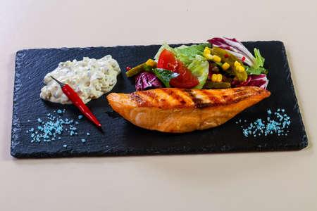 Grilled salmon steak with sauce Фото со стока