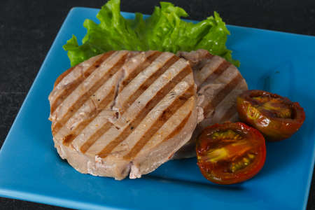 Grilled tuna steak with kumato and salad Фото со стока