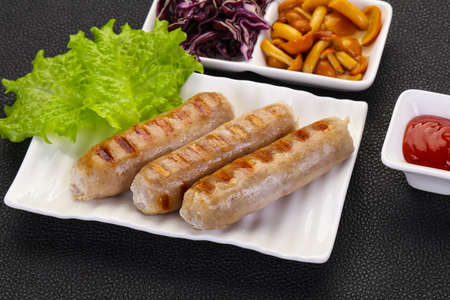 Grilled sausages served mushrooms, salad and cabbage Stock Photo - 129848953