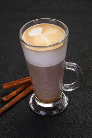 Capuccino in the glass served cinnamon sticks Stockfoto