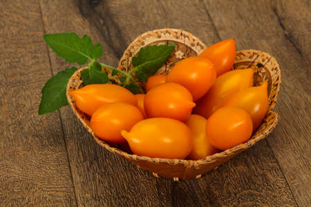 Ripe Yellow tomato heap in the wooden bowl