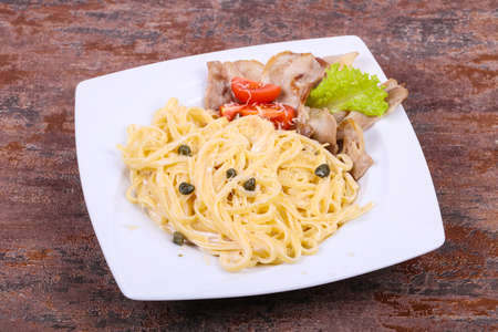 Pasta carbonara with bacon and cheese served capers