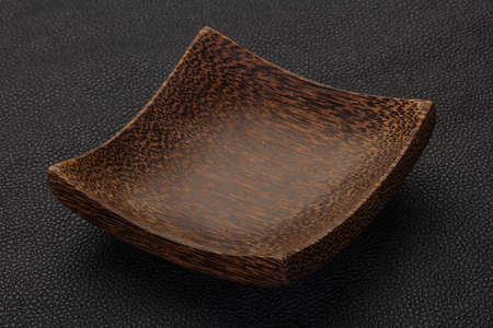 Empty wooden bowl over black background