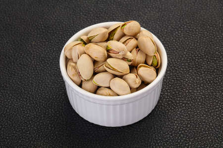 Pistachio nuts heap in the bowl Stock Photo