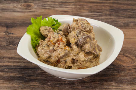 Chicken liver with cream and dry tomatoes served thyme Stock Photo