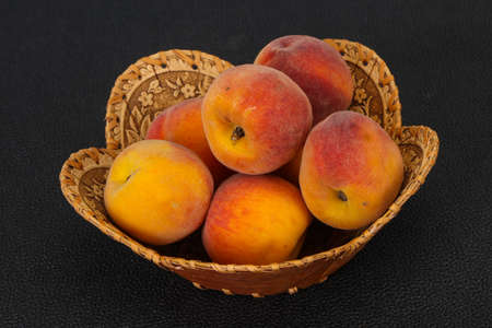 Ripe Peach heap in the wooden basket 写真素材