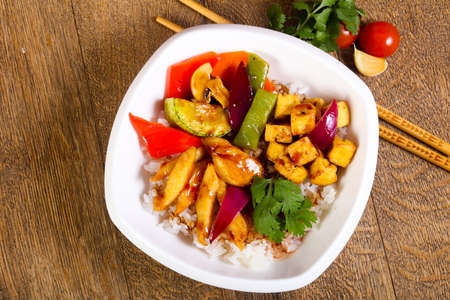 Wok with rice, vegetables, cheese and tofu