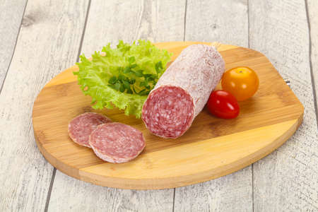 Italian dry Salami pork sausage served salad leaves Banco de Imagens