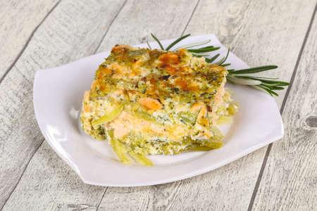 Leckerer Auflauf mit Lachs und Brokkoli serviert mit Rosmarin Standard-Bild