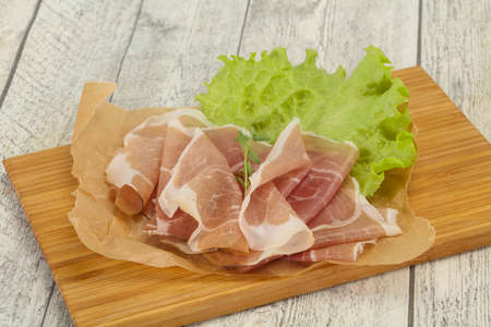 Italian prosciutto pork meat snack over board Foto de archivo - 135502708