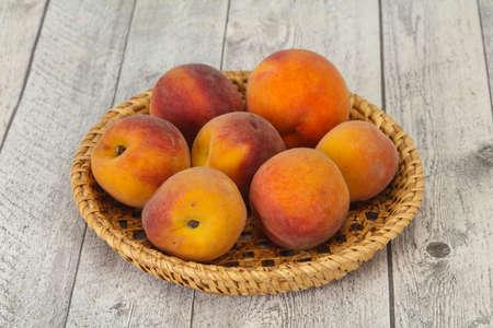 Ripe Peach heap in the wooden basket Reklamní fotografie