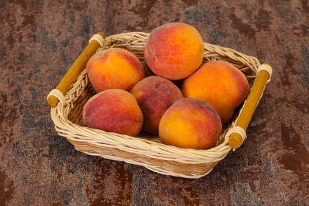 Ripe Peach heap in the wooden basket Stock Photo