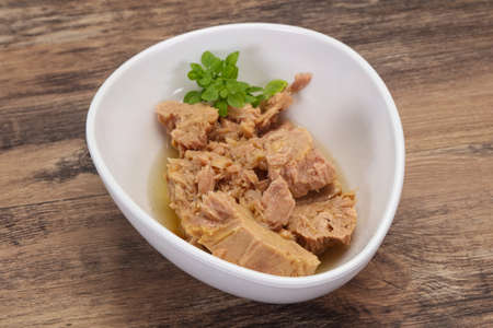 Canned tuna fish in the bowl served basil leaves