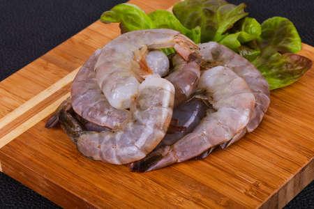 Crevettes royales crues prêtes à cuire les feuilles de salade servies Banque d'images