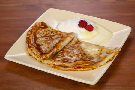 Pancakes with sour cream and condenced milk served berries