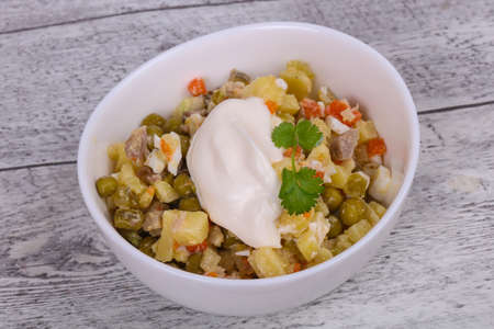 Traditional Russian salad with chicken in the white bowl over wooden background