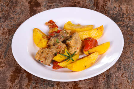 Baked pork meat with potao and tomato served rosemary Foto de archivo