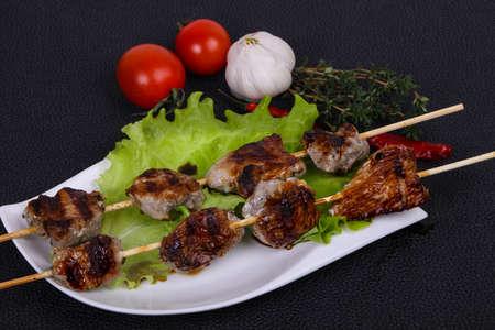 Pork kebab skewers in the plate with salad leaves and tomatoes served thyme and garkic Zdjęcie Seryjne