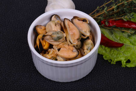 Pickled mussels in the bowl served pepper, garlic and salad leaves
