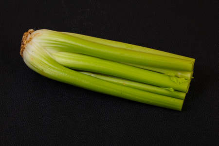 Organic food - celery sticks over wooden background