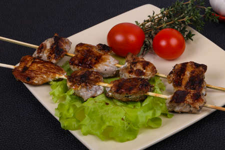 Pork kebab skewers in the plate with salad leaves and tomatoes served thyme and garkic Reklamní fotografie