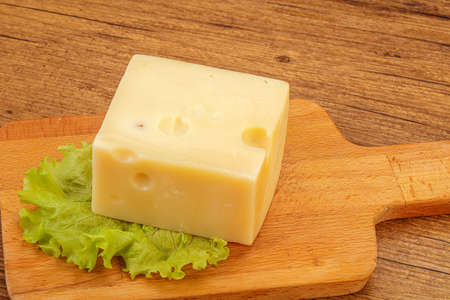 Emmental cheese over wooden board served salad  Archivio Fotografico
