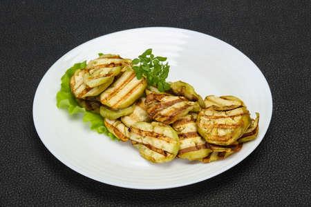 Grilled eggplant slices served basil and salad leaves