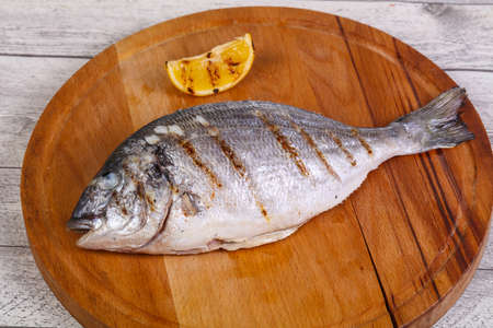 Grilled dorada with lemon over the wooden board