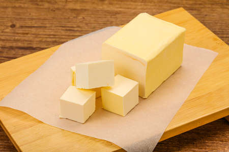 Dairy natural yellow butter piece over board