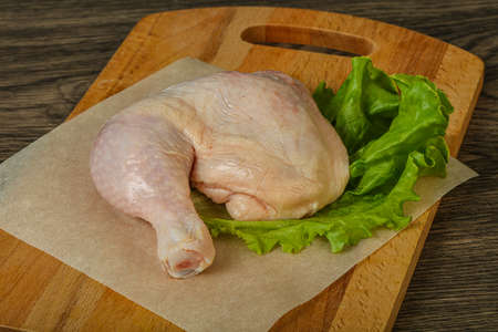 Raw chicken leg for cooking served salad leaves