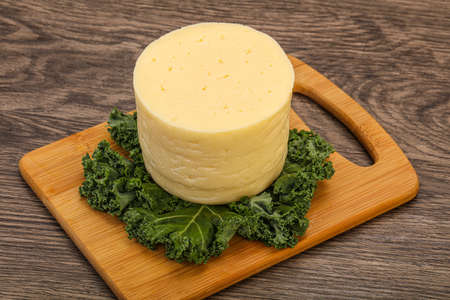 Yellow round dairy soft cheese piece
