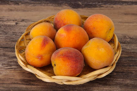 Ripe Peach heap in the wooden basket 스톡 콘텐츠