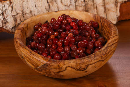 Traditional soaked cowberry in the wooden bowl