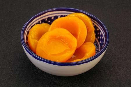 Marinated peaches fruit in the bowl with syrope