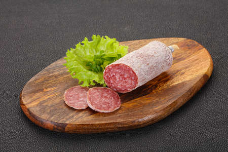 Italian dry Saliami pork sausage served salad leaves