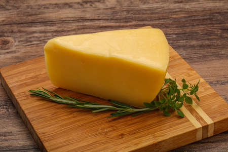 Hard cheese piece served rosemary and basil