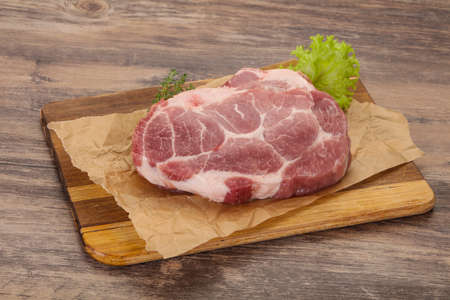 Raw pork steak over wooden board ready for cooking Stock fotó