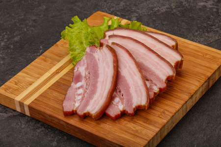 Tasty smoked pork brisket slice over wooden board