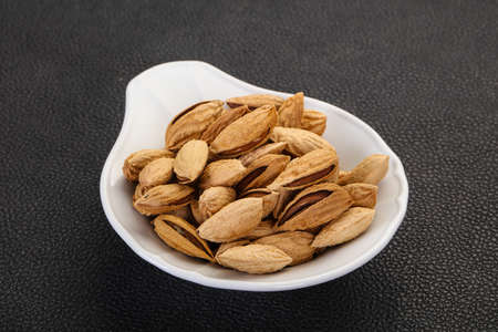 Unpeeled Almonds nuts heap in the bowl