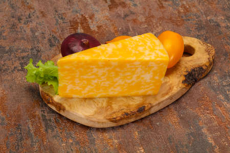 Marble cheese triangle over wooden background 스톡 콘텐츠