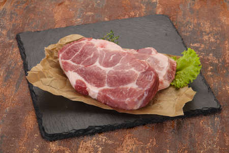 Raw pork steak over wooden board ready for cooking Banco de Imagens