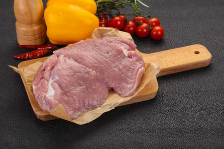 Raw pork meat over the wooden background