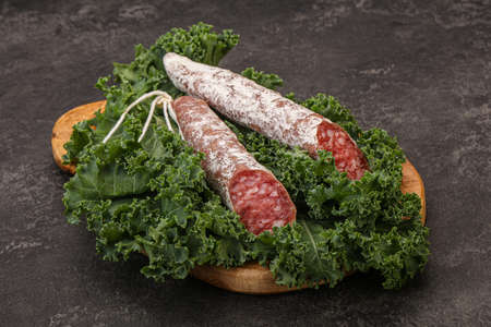 Spanish Fuet sausage with salad leaves over wooden background Stock fotó