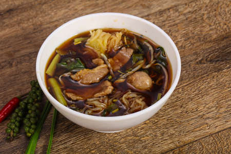 Thai style soup with meat, vegetables and mushrooms