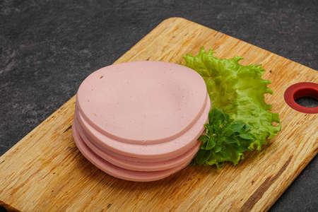 Sliced pork natural sausages over board served basil Reklamní fotografie