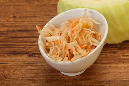 Pickled cabbage - sauerkraut in the bowl over wooden Banco de Imagens