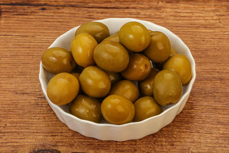 Green pickled olives heap in the bowl Banco de Imagens