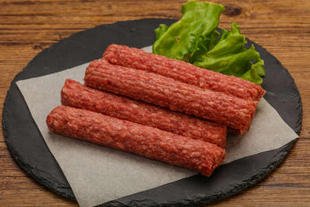 Raw beef sausages with spices for grill