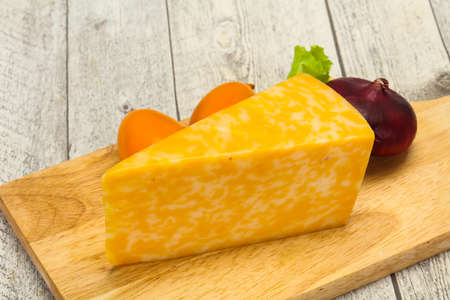Marble cheese triangle over wooden background 免版税图像